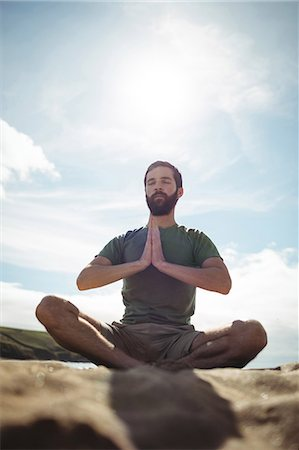 Man performing yoga on beach Stock Photo - Premium Royalty-Free, Code: 6109-08764009