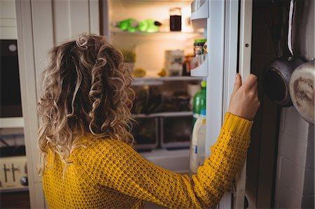 fridge - Woman looking for food in refrigerator in kitchen at home Stock Photo - Premium Royalty-Free, Code: 6109-08764415