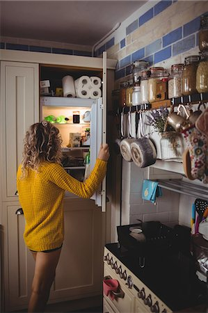 fridge - Woman looking for food in refrigerator in kitchen at home Stock Photo - Premium Royalty-Free, Code: 6109-08764416