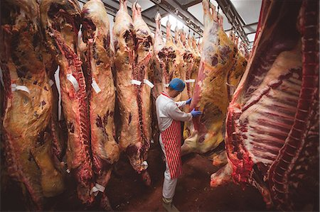 Butcher examining the red meat hanging in storage room at butchers shop Stock Photo - Premium Royalty-Free, Code: 6109-08764508