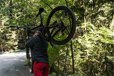 Male cyclist carrying mountain bike while walking in park Stock Photo - Premium Royalty-Free, Code: 6109-08764786