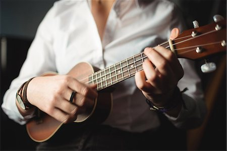 Mid-section of woman playing a guitar in music school Stock Photo - Premium Royalty-Free, Code: 6109-08764721