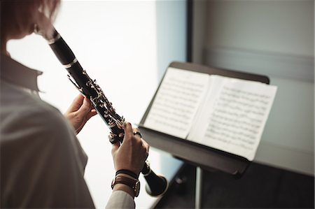 Mid-section of woman playing a clarinet in music school Stock Photo - Premium Royalty-Free, Code: 6109-08764736