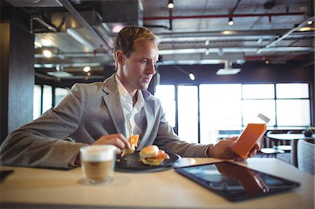 simsearch:6109-08700445,k - Businessman having breakfast in cafeteria during office hours Stock Photo - Premium Royalty-Free, Code: 6109-08765108