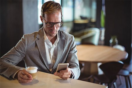simsearch:6109-08700445,k - Businessman using mobile phone while having coffee at café Stock Photo - Premium Royalty-Free, Code: 6109-08765109