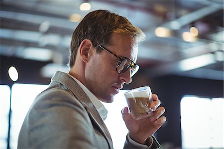 simsearch:6109-08700445,k - Confident businessman having coffee at café Stock Photo - Premium Royalty-Free, Code: 6109-08765111