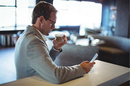 simsearch:6109-08700445,k - Businessman using mobile phone while having coffee at café Stock Photo - Premium Royalty-Free, Code: 6109-08765112