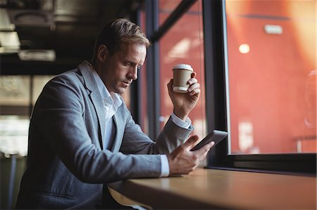 simsearch:6109-08700445,k - Businessman using mobile phone while having coffee at café Stock Photo - Premium Royalty-Free, Code: 6109-08765117