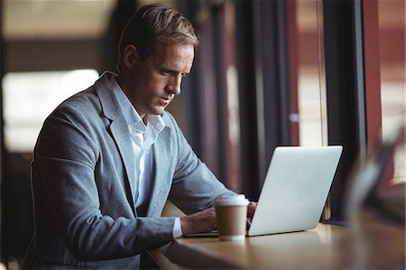simsearch:6109-08700445,k - Confident businessman working on laptop with a coffee on table Stock Photo - Premium Royalty-Free, Code: 6109-08765118