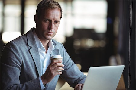 simsearch:6109-08700445,k - Portrait of businessman working on laptop while having coffee at café Stock Photo - Premium Royalty-Free, Code: 6109-08765119