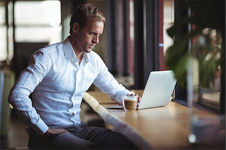 simsearch:6109-08700445,k - Confident businessman working on laptop with a coffee on table Stock Photo - Premium Royalty-Free, Code: 6109-08765121