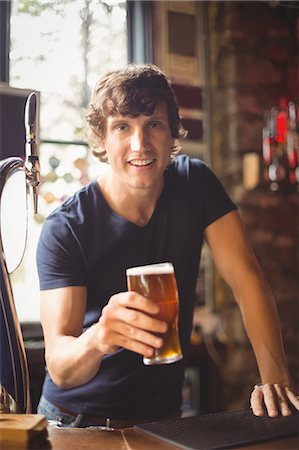 Portrait of man holding glass of beer at bar Stock Photo - Premium Royalty-Free, Code: 6109-08782637
