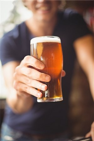 Close-up of man holding glass of beer at bar Stock Photo - Premium Royalty-Free, Code: 6109-08782639