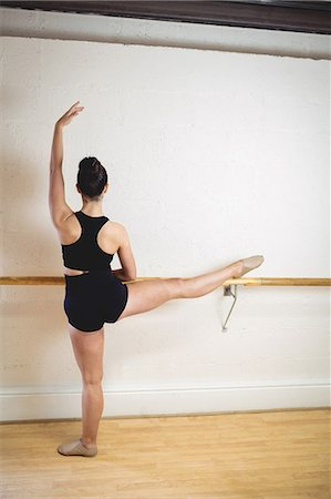 Ballerina stretching on a barre while practising ballet dance in the studio Stock Photo - Premium Royalty-Free, Code: 6109-08782821