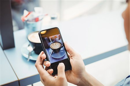 female hand - Woman holding mobile phone with photograph of coffee at restaurant Stock Photo - Premium Royalty-Free, Code: 6109-08700238