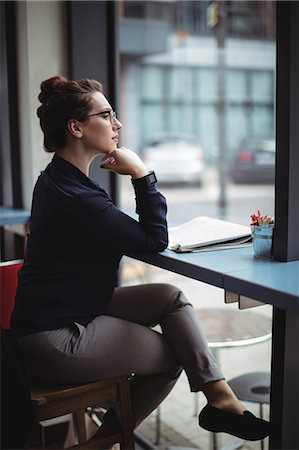 simsearch:6109-08700445,k - Businesswoman sitting by table in cafe Stock Photo - Premium Royalty-Free, Code: 6109-08700443