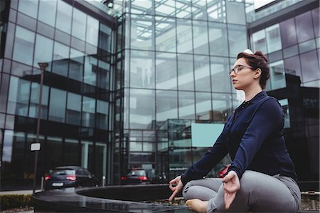 simsearch:6109-08700445,k - Full length of businesswoman doing yoga against office building Stock Photo - Premium Royalty-Free, Code: 6109-08700440