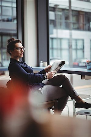 simsearch:6109-08700445,k - Businesswoman holding newspaper while sitting on chair in cafe Stock Photo - Premium Royalty-Free, Code: 6109-08700442
