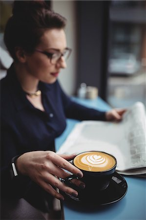 restaurant - Young businesswoman with coffee cup reading newspaper in cafe Stock Photo - Premium Royalty-Free, Code: 6109-08700445