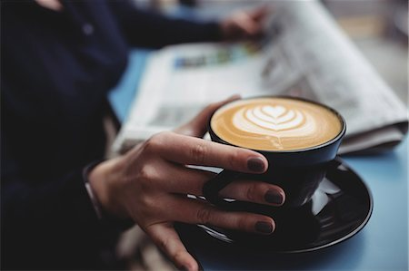 simsearch:6109-08700445,k - Midsection of woman holding coffee cup in cafe Stock Photo - Premium Royalty-Free, Code: 6109-08700446
