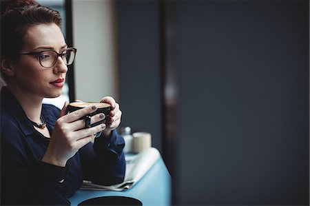 simsearch:6109-08700445,k - Thoughtful businesswoman holding coffee cup in cafe Stock Photo - Premium Royalty-Free, Code: 6109-08700448
