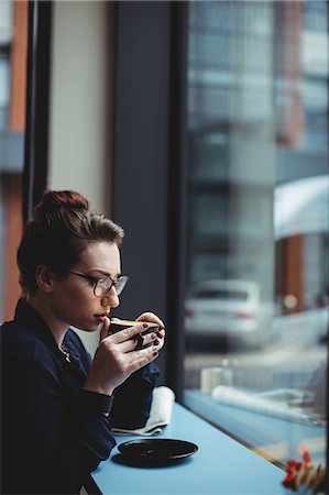 simsearch:6109-08700445,k - Thoughtful businesswoman drinking coffee in cafe Stock Photo - Premium Royalty-Free, Code: 6109-08700449