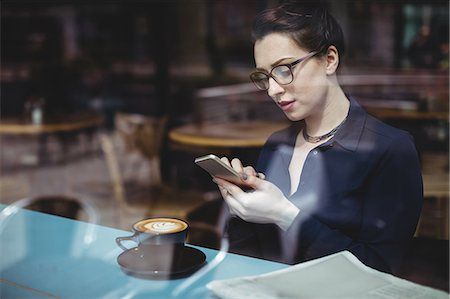 simsearch:6109-08700445,k - Young woman using mobile phone in cafe seen through glass Stock Photo - Premium Royalty-Free, Code: 6109-08700453