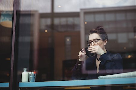 simsearch:6109-08700445,k - Thoughtful young woman drinking coffee in cafe seen through glass Stock Photo - Premium Royalty-Free, Code: 6109-08700450