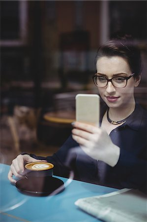 simsearch:6109-08700445,k - Young woman taking selfie in cafe seen through glass Stock Photo - Premium Royalty-Free, Code: 6109-08700452