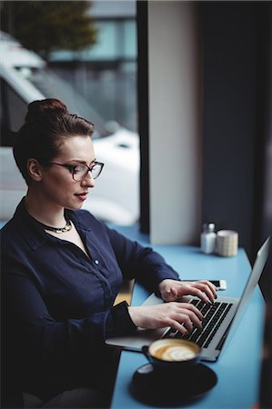 simsearch:6109-08700445,k - Beautiful businesswoman using laptop in cafe Stock Photo - Premium Royalty-Free, Code: 6109-08700457
