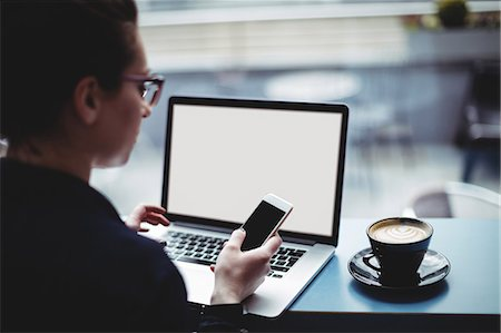 simsearch:6109-08700445,k - Woman with laptop using mobile phone at table in cafe Stock Photo - Premium Royalty-Free, Code: 6109-08700459