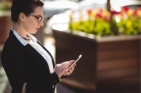simsearch:6109-08700445,k - Side view of young businesswoman using mobile phone Stock Photo - Premium Royalty-Free, Code: 6109-08700494