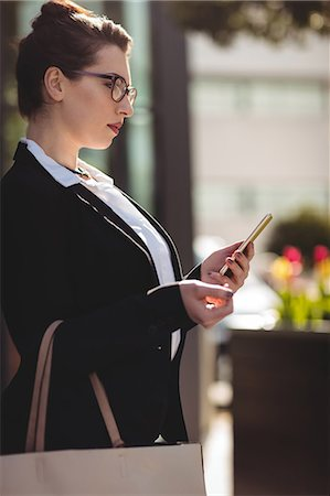 simsearch:6109-08700445,k - Young businesswoman with bag using mobile phone Stock Photo - Premium Royalty-Free, Code: 6109-08700495