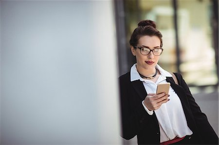simsearch:6109-08700445,k - Young businesswoman holding mobile phone while leaning on wall Stock Photo - Premium Royalty-Free, Code: 6109-08700496