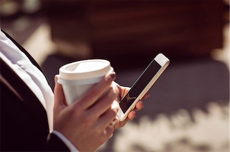 simsearch:6109-08700445,k - Cropped image of woman holding mobile phone and disposable coffee cup Stock Photo - Premium Royalty-Free, Code: 6109-08700498