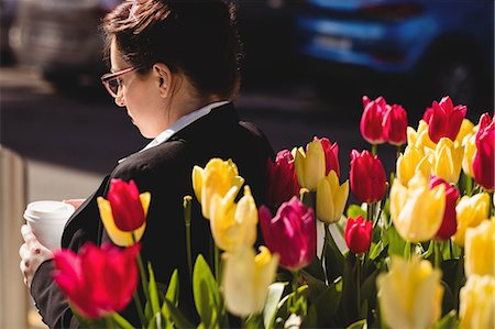 simsearch:6109-08700445,k - Young businesswoman standing by flowers Stock Photo - Premium Royalty-Free, Code: 6109-08700499