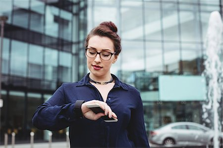 simsearch:6109-08700445,k - Businesswoman checking time outside office building Stock Photo - Premium Royalty-Free, Code: 6109-08700427
