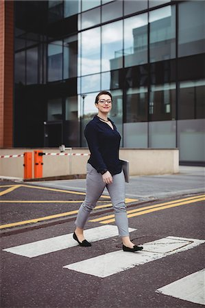 simsearch:6109-08700445,k - Full length portrait of confident businesswoman walking on road Stock Photo - Premium Royalty-Free, Code: 6109-08700424