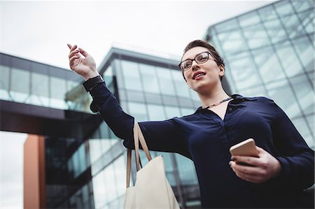 simsearch:6109-08700445,k - Low angle view of businesswoman gesturing outside office building Stock Photo - Premium Royalty-Free, Code: 6109-08700425