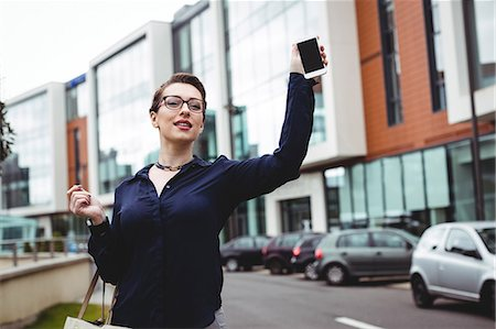 simsearch:6109-08700445,k - Businesswoman holding mobile phone by buildings on road Stock Photo - Premium Royalty-Free, Code: 6109-08700426