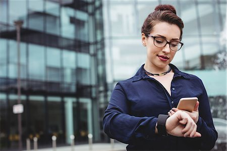 simsearch:6109-08700445,k - Businesswoman using mobile phone outside office building Stock Photo - Premium Royalty-Free, Code: 6109-08700428