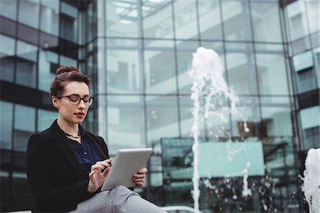 simsearch:6109-08700445,k - Businesswoman using digital tablet by fountain outside office building Stock Photo - Premium Royalty-Free, Code: 6109-08700432