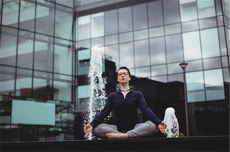 simsearch:6109-08700445,k - Full length of businessoman doing yoga against office building Stock Photo - Premium Royalty-Free, Code: 6109-08700436