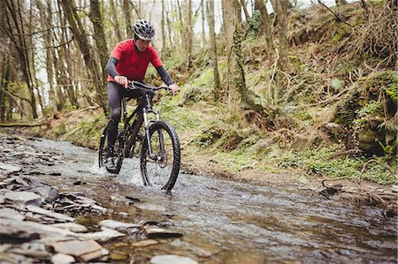 stream - Front view of mountain biker in stream amidst trees at forest Stock Photo - Premium Royalty-Free, Code: 6109-08700560