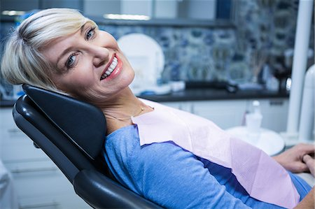 Smiling patient sitting on dentist's chair at clinic Stock Photo - Premium Royalty-Free, Code: 6109-08700846