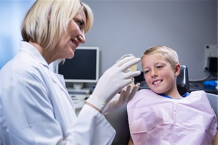 Dentist showing mouth model to patient at the dental clinic Stock Photo - Premium Royalty-Free, Code: 6109-08700836