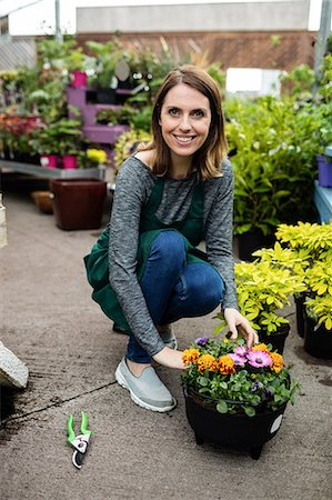 Portrait of happy female florist with potted plants in garden centre Stock Photo - Premium Royalty-Free, Code: 6109-08701153