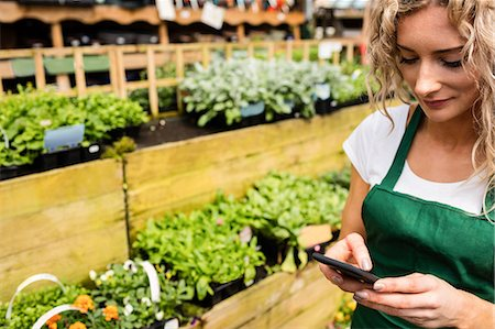 farm phone - Female florist using mobile phone in garden centre Stock Photo - Premium Royalty-Free, Code: 6109-08701169