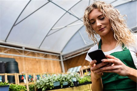 farm phone - Female florist using mobile phone in garden centre Stock Photo - Premium Royalty-Free, Code: 6109-08701170