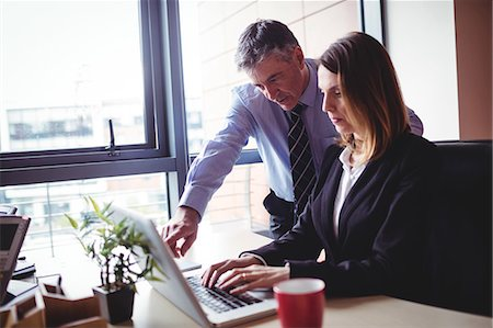 simsearch:6109-08700445,k - Businessman discussing with colleague over laptop in office Stock Photo - Premium Royalty-Free, Code: 6109-08701291